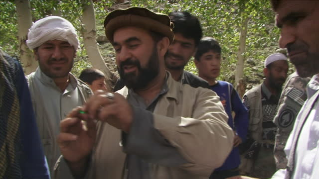 may 1 2009 ms man showing emeralds to crowd / panjshir valley afghanistan / audio - panjshir valley stock videos and b-roll footage