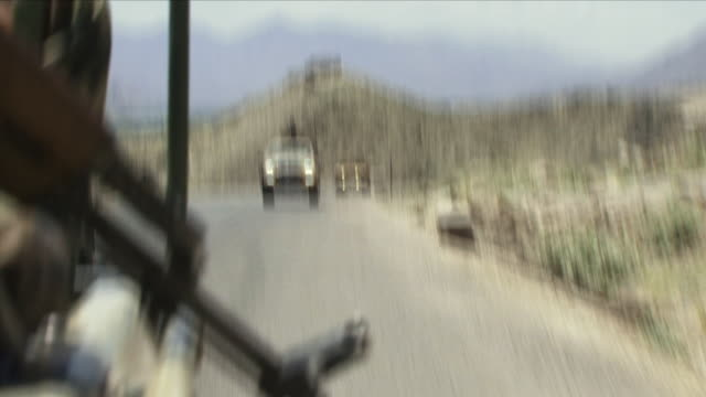 May 1 2009 CU REAR POV Military convoy with person holding gun in foreground / Konar Valley Afghanistan