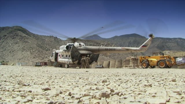 vidéos et rushes de may 1 2009 ws la soldiers standing next to helicopter in military base / najil afghanistan - uniforme militaire