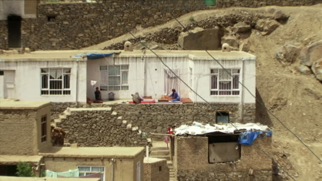 may 1 2009 ws zo ha women cleaning carpets in backyard with townscape / old kabul afghanistan - kabul stock-videos und b-roll-filmmaterial