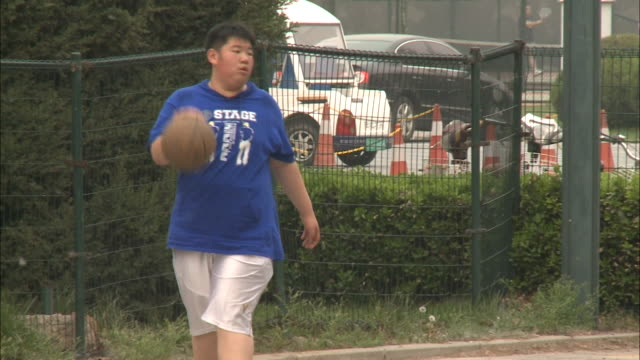 May 1 2010 TS A husky Chinese boy dribbling and shooting a basket at a court in a park / China