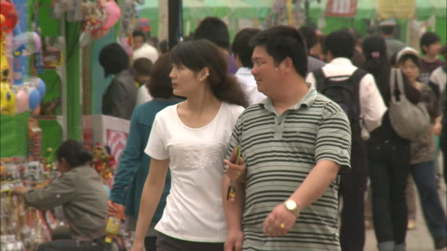 May 1 2010 TS A young couple strolling arm in arm through a street market / China