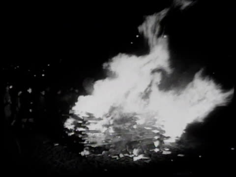 vídeos de stock, filmes e b-roll de may 10 1933 montage news announcer's voice is heard over the noise of brownshirts throwing jewish books into a bonfire / berlin, germany - 1933