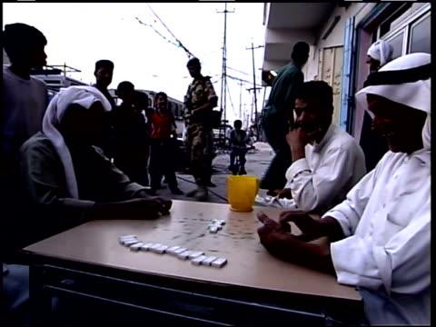 may 10 1999 montage cafe customers playing dominoes around table on sidewalk / iraq - bordsyteinspelning bildbanksvideor och videomaterial från bakom kulisserna