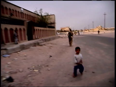 May 10 1999 POV US Army soldiers patrolling next to burnedout building with children running alongside singing waving and smiling / Iraq