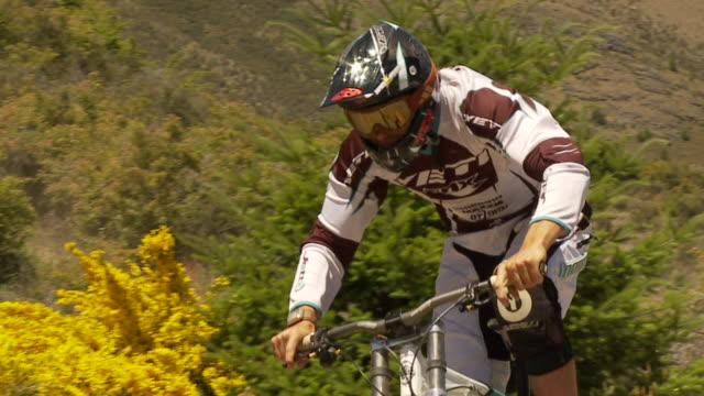 may 11 2009 montage professional downhill mountain bike racer making a fast paced run with freestyle jumps in rough terrain - mountain bike video stock e b–roll