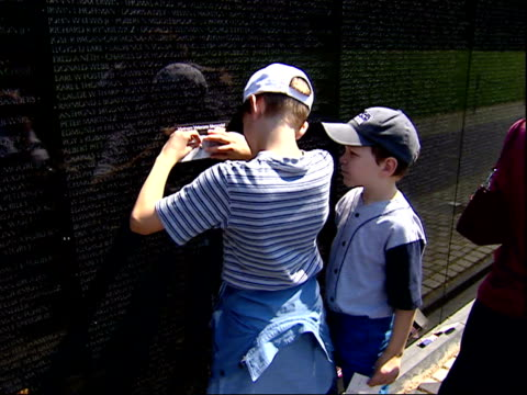 may 12, 2004 child rubbing a name from the vietnam memorial wall onto a piece of paper / washington, d.c., united states - vietnam veterans memorial video stock e b–roll