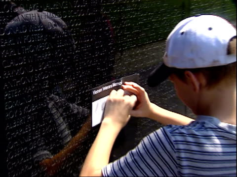 may 12, 2004 child showing his rubbing of a name from the vietnam memorial wall to others / washington, d.c., united states - vietnam veterans memorial video stock e b–roll
