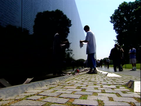 may 12, 2004 tourist rubbing name off the vietnam memorial wall / washington, d.c., united states - 戦争記念碑点の映像素材/bロール