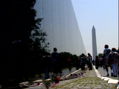 may 12, 2004 tourists walking along vietnam memorial wall with washington monument in background / washington, d.c., united states - vietnam veterans memorial video stock e b–roll