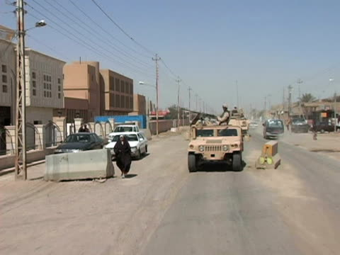 May 13 2004 WS ZI ZO REAR POV Soldiers patrolling streets Baghdad Iraq AUDIO