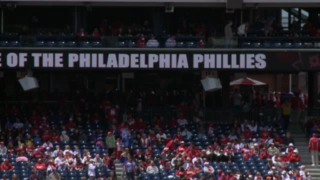vídeos de stock e filmes b-roll de may 13 2010 montage baseball fans filling seats and watching scoreboard monitor at citizens bank park / philadelphia pennsylvania united states - encontrar