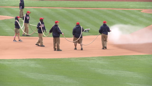 may 13 2010 ws phillies' grounds crew wetting down infield with hose at citizens bank park / philadelphia pennsylvania united states - philadelphia phillies stock-videos und b-roll-filmmaterial