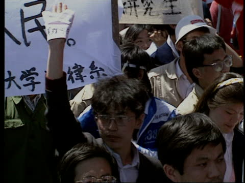 may 14 1989 film montage ms pan protestors in tiananmen square/ cu protestors holding up wads of banknotes/ ms protestor holding up sign to camera/... - anno 1989 video stock e b–roll