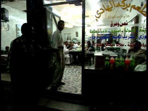 may 14 1999 montage cook preparing food on a rotisserie outside a restaurant where diners are eating / nasiriyah iraq - nasiriyah stock-videos und b-roll-filmmaterial