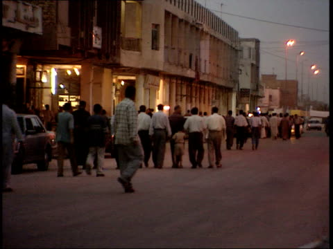 vídeos de stock e filmes b-roll de may 14, 1999 pedestrians walking past lit buildings at dusk / nasiriyah, iraq - back lit