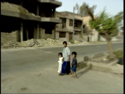 may 15 1999 ts children holding hands and walking past rubble and bombedout buildings / nasiriyah iraq - nasiriyah stock-videos und b-roll-filmmaterial