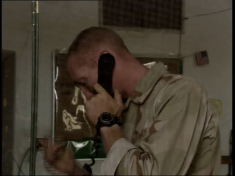 may 15 1999 zo us army soldier talking on the phone at the police station / nasiriyah iraq - nasiriyah stock-videos und b-roll-filmmaterial