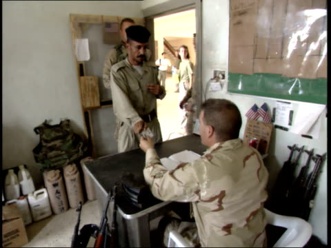 may 16 2003 td us army officer issuing firearms to the iraqi police officers / nasiriyah iraq - nasiriyah stock-videos und b-roll-filmmaterial