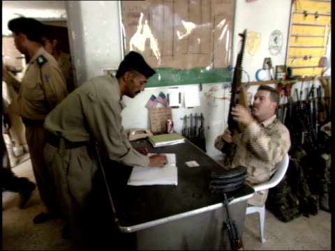 may 16 2003 zi us army officer issuing rifles to iraqi police officers / nasiriyah iraq - nasiriyah stock-videos und b-roll-filmmaterial