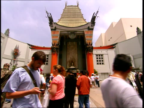 stockvideo's en b-roll-footage met may 18, 2006 montage pedestrians walking outside of mann's chinese theater and interacting with celebrity impersonators / los angeles, california,... - tcl chinese theatre