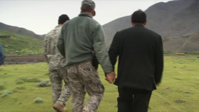 vídeos de stock e filmes b-roll de may 18 2009 ms pov american soldier and afghan soldier holding hands and walking / panjshir valley afghanistan / audio - só homens maduros