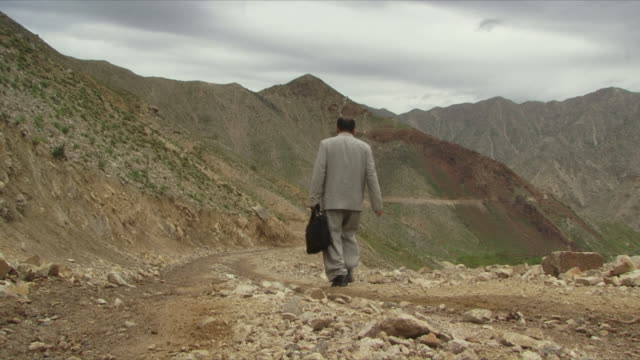 stockvideo's en b-roll-footage met may 18 2009 ws businessman walking to work down dirt road through mountains / panjshir valley afghanistan / audio - grind