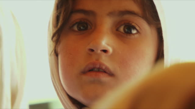 stockvideo's en b-roll-footage met may 18 2009 cu girl in headscarf looking at camera / panjshir valley afghanistan / audio - hoofddoek