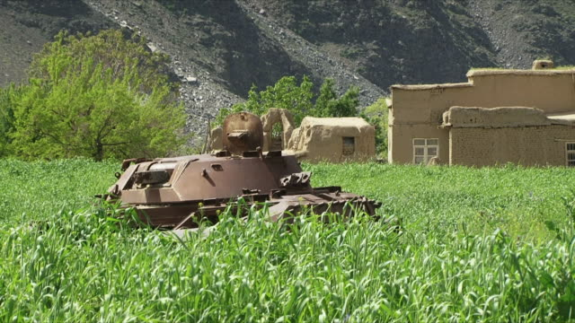 may 18 2009 ws zi local women walking past deactivated tank in field / panjshir valley afghanistan / audio - panjshir valley stock videos and b-roll footage