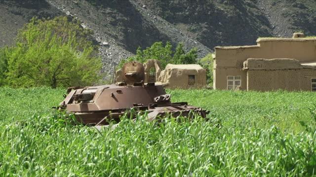 vídeos y material grabado en eventos de stock de may 18 2009 ws zi local women walking past deactivated tank in field / panjshir valley afghanistan / audio - vehículo acorazado