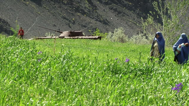 may 18 2009 ws local women walking past deactivated tank in field / panjshir valley afghanistan / audio - panjshir valley stock videos and b-roll footage