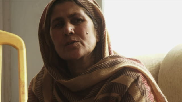 may 18 2009 ms portrait of mature woman sitting in room / panjshir valley afghanistan / audio - panjshir valley stock videos and b-roll footage