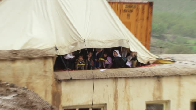may 18 2009 ws zo schoolchildren crouching under canvas protecting from rain / panjshir valley afghanistan / audio - schoolgirl stock videos & royalty-free footage