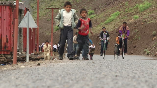 may 18 2009 ws schoolchildren running down country road / panjshir valley afghanistan / audio - panjshir valley stock videos and b-roll footage