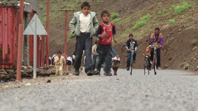 may 18 2009 ws schoolchildren running down country road / panjshir valley afghanistan / audio - schulkind nur jungen stock-videos und b-roll-filmmaterial