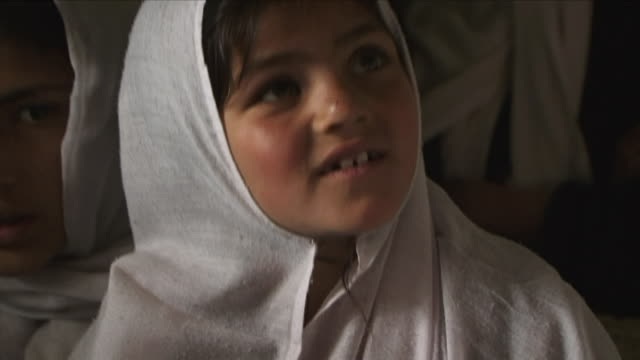 vidéos et rushes de may 18 2009 cu schoolgirl wearing headscarf looking around / panjshir valley afghanistan / audio - écolière