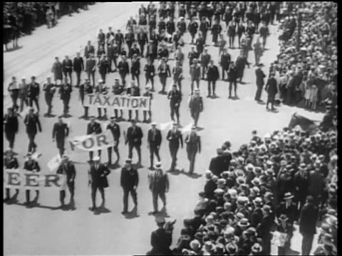 b/w may 1932 high angle people marching in beer parade carrying signs beer for taxation / 5th ave nyc - 禁酒法点の映像素材/bロール