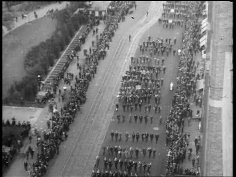 b/w may 1932 high angle tilt up long shot rows of people marching past crowds in beer parade / nyc - 1932 stock videos & royalty-free footage