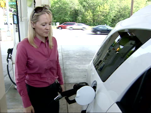 stockvideo's en b-roll-footage met may 2 2007 pan driver filling her tank with gas as the meter registers price and gallons at a bp amoco gas station / united states - benzineprijzen
