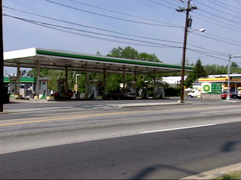 stockvideo's en b-roll-footage met may 2 2007 ws vehicles driving past a bp amoco gas station / united states - benzineprijzen