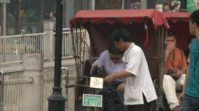 May 2 2010 TS A passenger boarding a pedicab and the driver taking him for a ride on a congested street / China