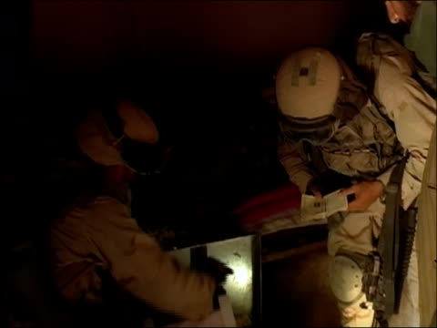 may 2004 close up zoom out us soldiers searching room with flashlight/ oruzgan province, afghanistan/ audio - searching点の映像素材/bロール