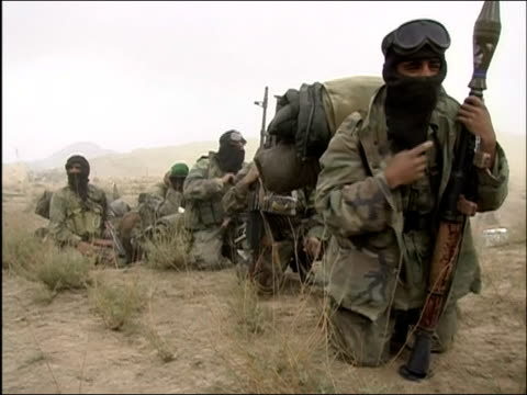 May 2004 Long shot Afghan National Army soldiers on their knees wearing balaclavas / Oruzgan Province Aghanistan / AUDIO