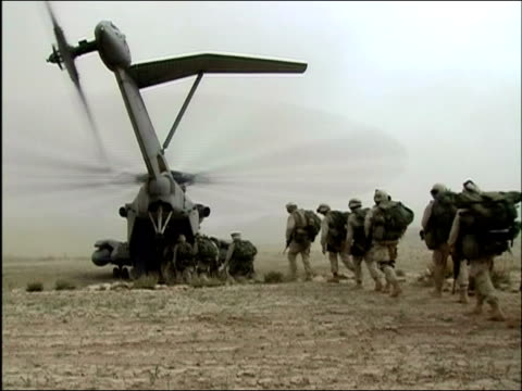 stockvideo's en b-roll-footage met may 2004 long shot us troops walking single file over dusty terrain and boarding helicopter / oruzgan province, aghanistan / audio - operation enduring freedom