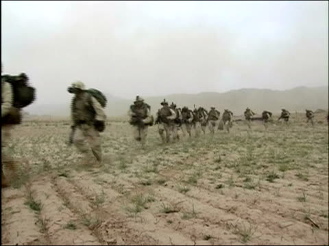 may 2004 long shot zoom in us troops running single file over dusty terrain / oruzgan province aghanistan / audio - 2004年点の映像素材/bロール