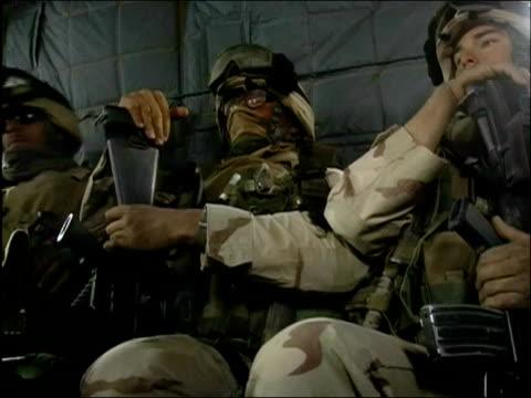 vídeos y material grabado en eventos de stock de may 2004 low angle medium shot us troops sitting aboard helicopter / putting on goggles / oruzgan province, aghanistan / audio - sólo hombres jóvenes