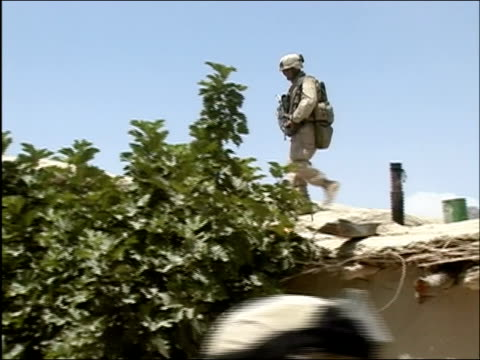 may 2004 low angle wide shot soldier walking across rooftop with rifle/ oruzgan province afghanistan/ audio - operazione enduring freedom video stock e b–roll