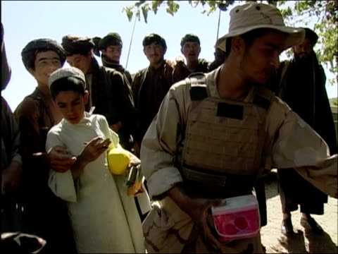 may 2004 medium shot afghan boys beg for toys being distributed by us troops/ oruzgan province afghanistan/ audio - operazione enduring freedom video stock e b–roll