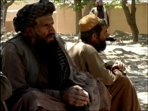 may 2004 medium shot afghan prisoners in plastic wrist restraints sitting next to each other/ oruzgan province afghanistan/ audio - operazione enduring freedom video stock e b–roll