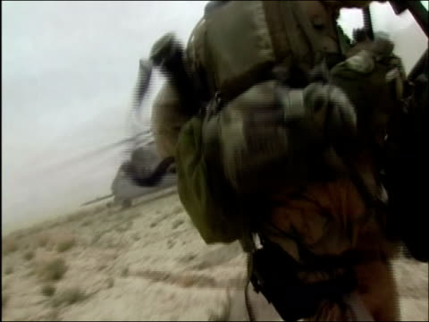 May 2004 Medium shot point of view US Troops running single file over dusty terrain and boarding helicopter / Oruzgan Province Aghanistan / AUDIO